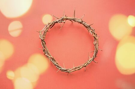 Crown of thorns like Jesus Christ wore with drops of blood on tips of thorns with bokeh lights over coral background. Perfect for Easter. Image shot from top view.