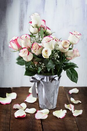 Beautiful bouquet of  red and white roses with babys breath in a metal farmhouse style vase surrounded by fallen petals.