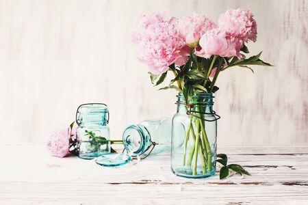 Hermosas flores de peonía rosa en un tarro de albañil azul antiguo sobre un fondo de mesa de madera rústica blanca con espacio para copiar el texto. Imagen editada para darle estilo a la decoración de una casa de campo.
