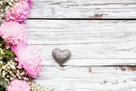 Pink Peonies, Babys Breath flowers and heart over a white rustic wood table background  with copy space for your text. Flat lay.