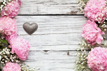 Pink Peonies, Baby's Breath flowers and heart over a white rustic wood table background  with copy space for your text. Flat lay.