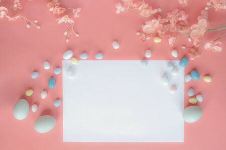 Pastel Easter eggs, malt candy covered chocolate eggs, and flower blossoms over a coral colored background with a blank card for copy space. Image shot from top view. Stockfoto