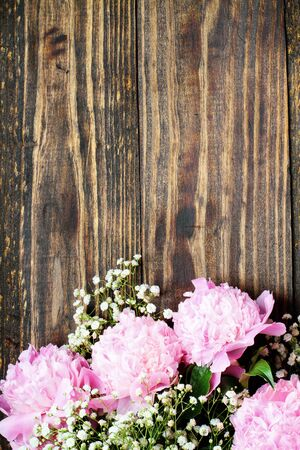 Pink Peonies and Baby's Breath flowers over a rustic wood table background  with copy space for your text. Flat lay.