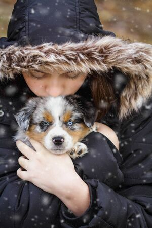 Beautiful teenage girl holds her six week old little dog in the snow outdoors. Selective focus on the Australian Shepherd puppys face. He has one blue eye and one green. Stockfoto