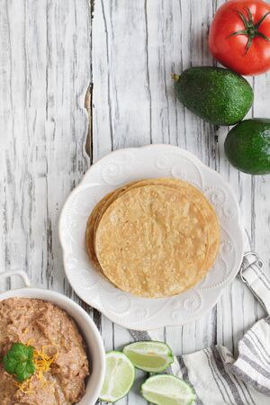Corn tortillas with refried beans, avocados, tomatoes and fresh limes to make vegan tostadas. Photo shot from top view. Stockfoto