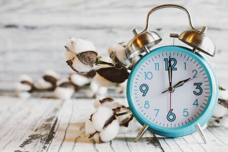 Set your clocks back with this clock iand bolt of cotton over a white wooden table. Daylight saving time concept. Selective focus with blurred background.