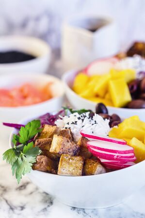 Healthy vegan poke bowl or Buddha bowl with basmati rice, mango, fried tofu, purple cabbage, radishes, kalamata olives, pickled ginger and black sesame seeds. Selective focus on tofu with blurred background.
