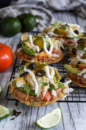 Homemade chicken tostadas with refried pinto beans, fresh cilantro, shredded cheddar cheese, avocados, black olives, sour cream, lettuce, jalapenos, lime and tomatoes. Selective focus with blurred background.