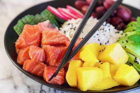 Hawaiian poke bowl with basmati rice, mango, raw salmon, avocado. radishes, cucumber, kalamata olives, pickled ginger and black sesame seeds. Selective focus on fish with blurred background and foreground. Stockfoto