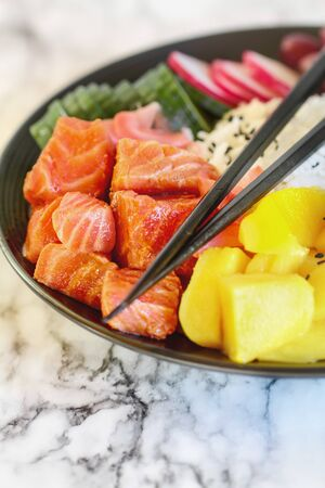 Hawaiian poke bowl with basmati rice, mango, raw salmon, radishes, cucumber, kalamata olives, pickled ginger and black sesame seeds. Selective focus on fish with blurred background and foreground.