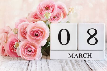 White wood calendar blocks with the date March 08 for International Womens Day and pink ranunculus flowers over a wooden table. Stockfoto