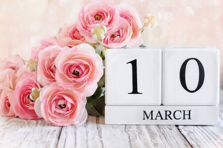 White wood calendar blocks with the date March 10th and pink ranunculus flowers over a wooden table. Selective focus with blurred background.