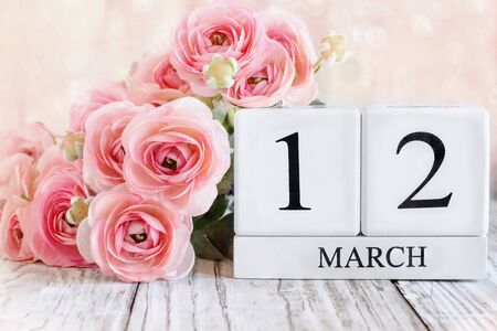 White wood calendar blocks with the date March 12th and pink ranunculus flowers over a wooden table. Selective focus with blurred background.