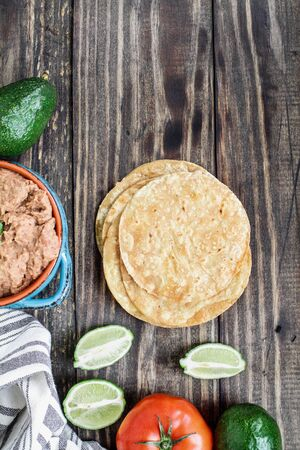 Ingredients of fried corn tortillas, refried beans, avocados, tomatoes and fresh limes for making vegan Tostadas. Top view, flatlay.