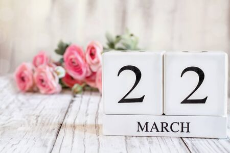 White wood calendar blocks with the date March 22 th for Mothers Day or Mothering Sunday 2020 . Selective focus with pink ranunculus in the background over a wooden table.