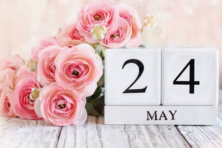 White wood calendar blocks with the date May 24th and pink ranunculus flowers over a wooden table. Selective focus with blurred background.