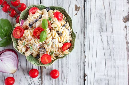 Top view of Pasta Salad with freshly chopped basil, tomatoes, black olives, red onion and Feta cheese, tossed with an Italian oil dressing.