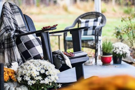 Adirondack rocking chair with traditional style buffalo check blanket and pillows on a porch or patio decorated for autumn with heirloom gourds and white and orange mums. Selective focus with garden blurred in the background. Archivio Fotografico