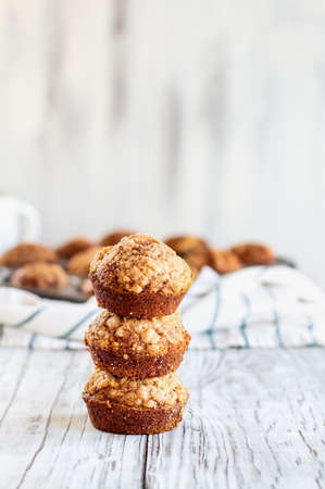 Beautiful fresh baked homemade pumpkin muffins stack on top of each other against a white background. Selective focus on bread in front with blurred background.