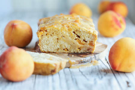 Delicious homemade peach sweet bread with frosting and fresh peaches. Selective focus with blurred foreground and background.