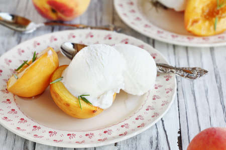 Overhead view of fresh homemade roasted peaches baked in brown sugar and fresh rosemary sprigs and served with vanilla ice cream. Selective focus with blurred background.