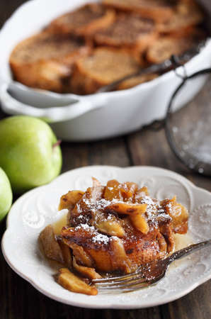 Serving of apple French toast casserole with maple syrup and powdered sugar. Selective focus with blurred background. Archivio Fotografico