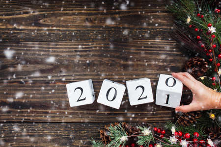Woman's hand flipping New Year's 2020 wood calendar blocks to 2021. Christmas tree lights, pine branches, red winter berries and snow. Top view.