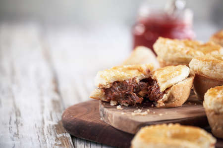 Cut fresh venison meat pies on a rustic wood cutting board with filling visible and ketchup in the background. Selective focus on center pie with extreme blurred foreground and background. Free space for text available. Stockfoto