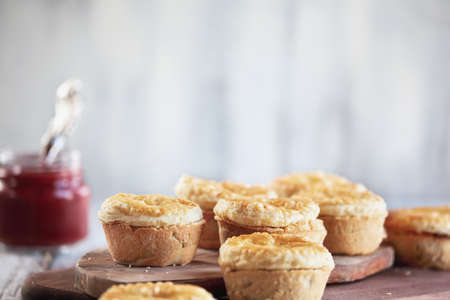 Fresh meat pies on a rustic wood cutting board with ketchup in the background. Selective focus on center pie with extreme blurred foreground and background. Free space for text available.