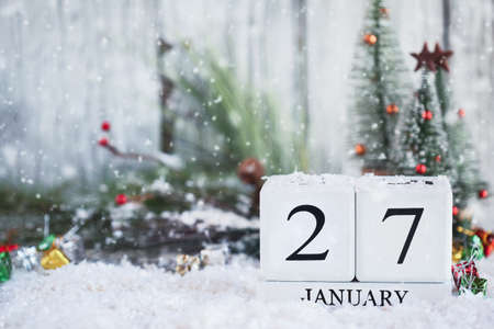 White wood calendar blocks with the date January 27th and Christmas decorations with snow. Selective focus with blurred background.