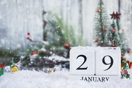White wood calendar blocks with the date January 29th and Christmas decorations with snow. Selective focus with blurred background.