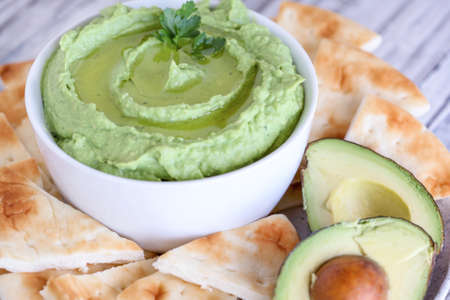 Vegan avocado Hummus, made with chickpeas, avocados and tahini, with olive oil. Garnished with parsley and served with pita bread over a rustic table. Extreme shallow depth of field with background.