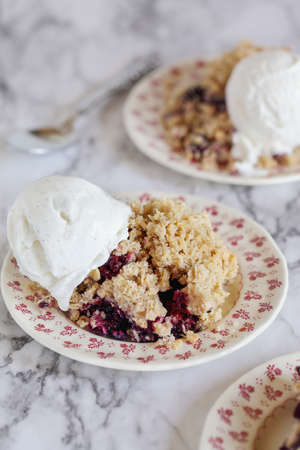 Blackberry and Blueberry Cobbler topped with a golden oatmeal crisp with ice cream. Extreme selective focus with blurred background.