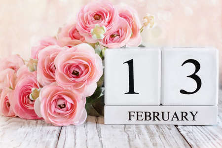 White wood calendar blocks with the date February 13th and pink ranunculus flowers over a wooden table. Selective focus with blurred background. Stockfoto