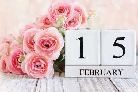 White wood calendar blocks with the date February 15th for International Childhood Cancer Awareness Day and pink ranunculus. Selective focus with blurred background. Stockfoto