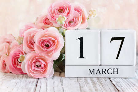White wood calendar blocks with the date March 17th and pink ranunculus flowers over a wooden table. Selective focus with blurred background.