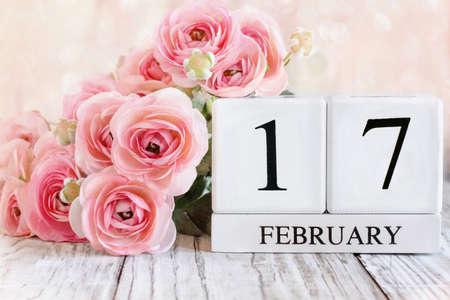 White wood calendar blocks with the date February 17th and pink ranunculus flowers over a wooden table. Selective focus with blurred background. Stockfoto