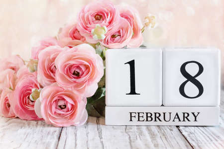 White wood calendar blocks with the date February 18th and pink ranunculus flowers over a wooden table. Selective focus with blurred background. Stockfoto