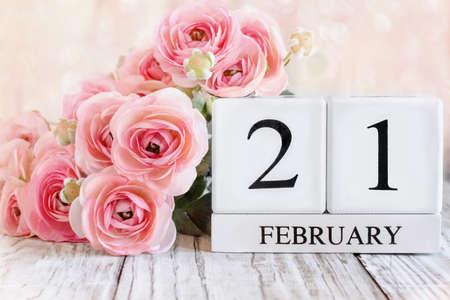 White wood calendar blocks with the date February 21st and pink ranunculus flowers over a wooden table. Selective focus with blurred background.