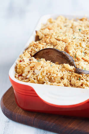 Fresh cheesy tuna casserole with pasta, buttery cracker crumbs and fresh herbs. Could also be used for chicken or ham. Selective focus with blurred background. Stockfoto