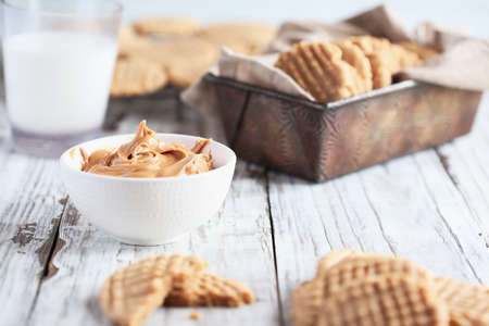 Bowl of creamy peanut butter with fresh baked, homemade cookies. Selective focus on spread in center with blurred foreground and background.
