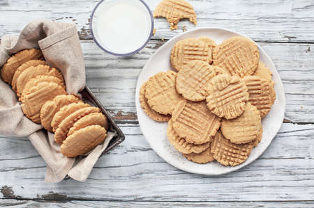 Flatlay of fresh baked, homemade peanut butter cookies and milk over a white rustic table. Image shot from up above, top view.