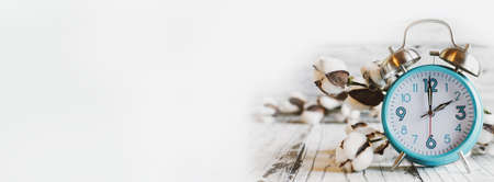 Set your clocks back with this banner of a clock and cotton over a white wooden table. Daylight saving time concept. Selective focus with blurred background. Stockfoto