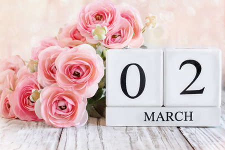 White wood calendar blocks with the date March 02 and pink ranunculus flowers over a wooden table. Selective focus with blurred background.