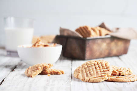 Fresh baked, homemade peanut butter cookies and milk over a white rustic table. Selective focus with blurred background.