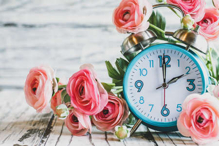 Set your clocks back with this clock and Ranunculus flowers over a white wooden table. Daylight saving time concept. Selective focus with blurred background. Stockfoto