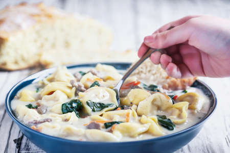 hand with Tortellini Soup with Italian sausage, spinach and carrots. Served with homemade artisan bread over a white wood wooden table. Selective focus on soup in spoon with blurred background.
