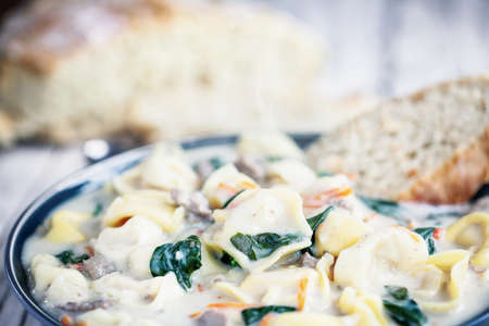 Fresh Tortellini Soup with Italian sausage, spinach and carrots. Served with homemade artisan bread over a white wood wooden table. Selective focus with blurred background.