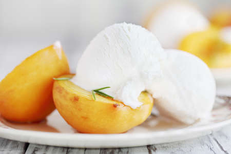 Fresh homemade roasted peaches baked in brown sugar and fresh rosemary sprigs and served with vanilla ice cream. Selective focus with blurred background. Stockfoto