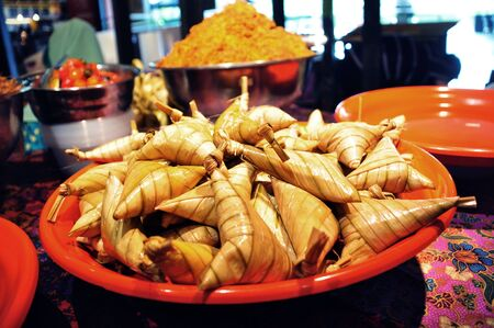 compressed rice: Ketupat Palas in a red plate for sale Stock Photo